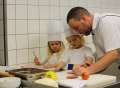 Vorschau: Ein Koch und ein Kind in der Küche.