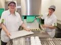 Vorschau: Zwei Mitarbeiterinnen entnehmen Tabletts vom Spülmaschinenband