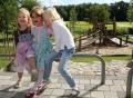 Vorschau: Im Vordergrund drei lachende Kitakinder, im Hintergrund der weitläufige Spielplatz.