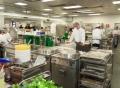 Vorschau: Küche der Mensa Golm mit Köchen und Köchinnen bei der Arbeit an Küchengroßgeräten