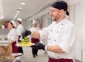 Vorschau: Koch garniert einen Teller an der Essenausgabe.