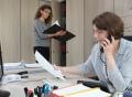 Vorschau: Zwei Mitarbeiterinnen im Büro, eine am Schreibtisch sitzend in einem telefonischen Gespräch, die andere stehend mit Aktenordner am Schrank