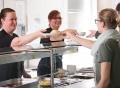 Vorschau: Mitarbeiterinnen an der Essenausgabe reichen Studentinnen das Menue über die Theke