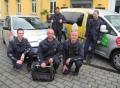 Vorschau: Das Hausmeister-/techniker-Team (5 Personen) auf dem Uni-Gelände, positioniert vor dem Umzugswagen des Studierendenwerks
