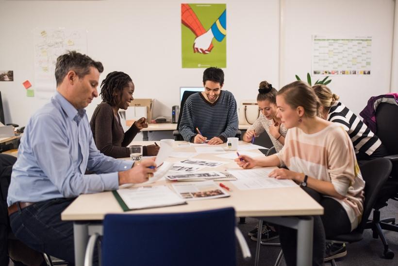 Beschäftigte und Studierende sitzen gemeinsam an einem Tisch und arbeiten an einem Kulturprojekt
