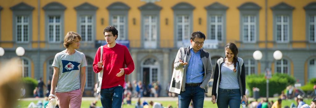 Studierende im Hofgarten vor dem Hauptgebäude der Universität Bonn