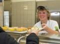 Vorschau: Freundliche Mitarbeiterin übergibt ein Mittagessen an einen Gast