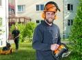 Vorschau: Hausmeister vor der Wohnanlage, im Vordergrund Hausmeister mit Sicherheitshelm und elektrischer Heckenschere, im Hintergrund ein weiterer Hausmeister mit Rasenmäher