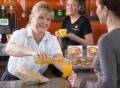 Vorschau: Freundliche Mitarbeiterin in der Kaffee-Insel bedient Kundin, im Hintergrund eine weitere Mitarbeiterin mit Kaffeetasse in der Hand