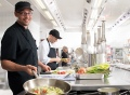 Vorschau: Im Vordergrund Koch, der durch geschicktes Anrucken der Pfanne den Inhalt wendet, ein weiterer Koch im Hintergrund schneidet Gemüse