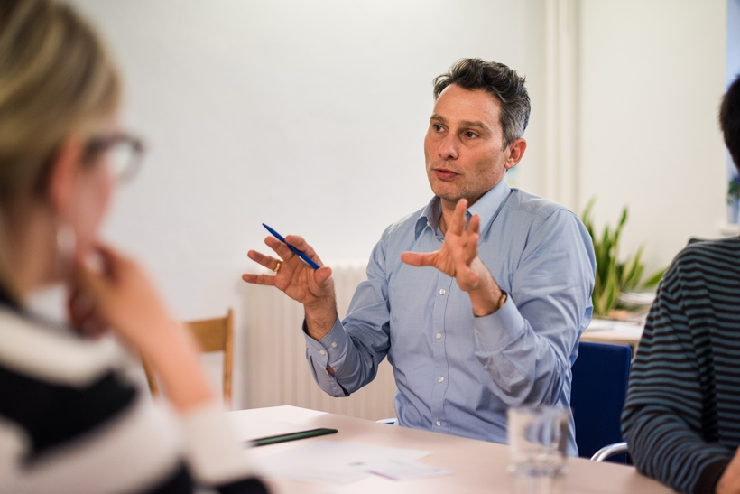 Ein Abteilungsleiter sitzt mit anderen am Tisch und erklärt mit großen Gesten