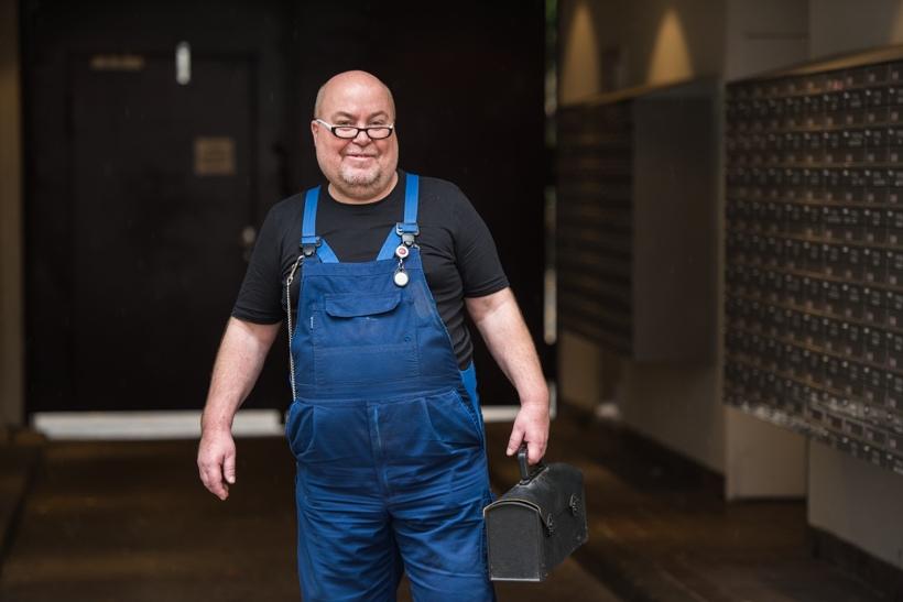 Hausmeister in blauer Arbeitslatzhose