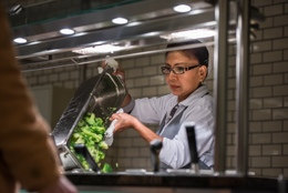 Mitarbeiterin an der Essensausgabe füllt frisches Gemüse in die Auslage
