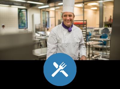 Ein Koch steht in der Großküche eines Studentenwerks und lächelt freundlich in die Kamera