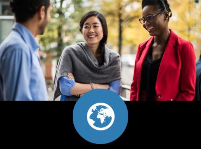 Drei Studierende, ein Mann und zwei Frauen, anscheinend aus verschiedenen Kulturen stehen beieinander und unterhalten sich