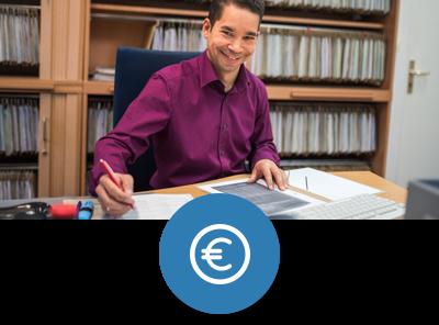 BAföG-Sachbearbeiter an seinem Schreibtisch, im Hintergrund Akten im Regal. Er schreibt in einem Aktenordner, schaut dabei lächelnd in die Kamera.