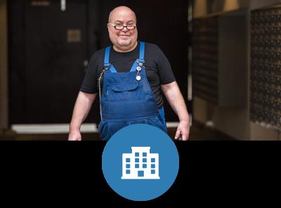 Ein Hausmeister steht im Eingangbereich einer Wohnanlage, in der Hand hält er einen Werkzeugkoffer. Er lächelt in die Kamera.