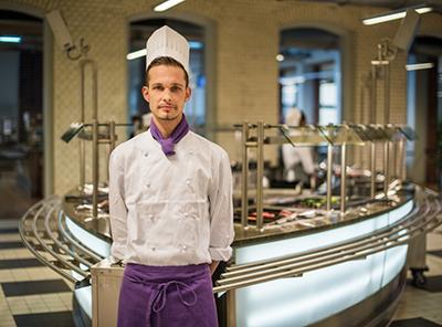 Koch in der Ausbildung, in weißer Kochjacke und Kochmütze mit lilafarbender Schürze steht im Bereich der Essensausgabe eines Studentenwerks