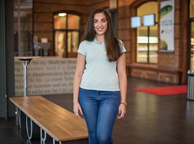 Praktikantin, steht im Foyer eines Studentenwerks und lächelt in die Kamera