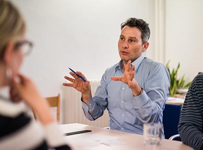 Abteilungsleiter instruiert mit weit ausladenden Gesten seine Mitarbeiter an einem Arbeitstisch